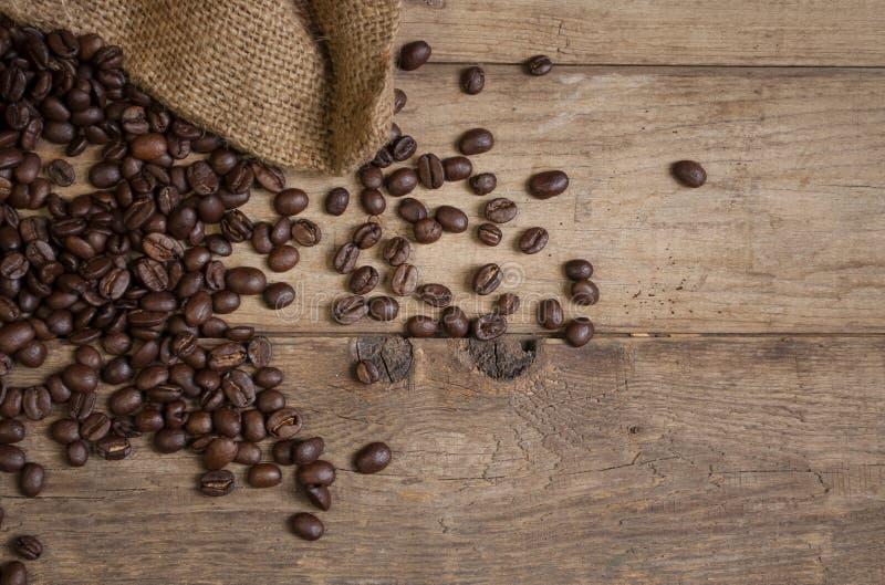 Quadro com feijões de café e uma xícara de café na madeira marrom natural fotos de stock