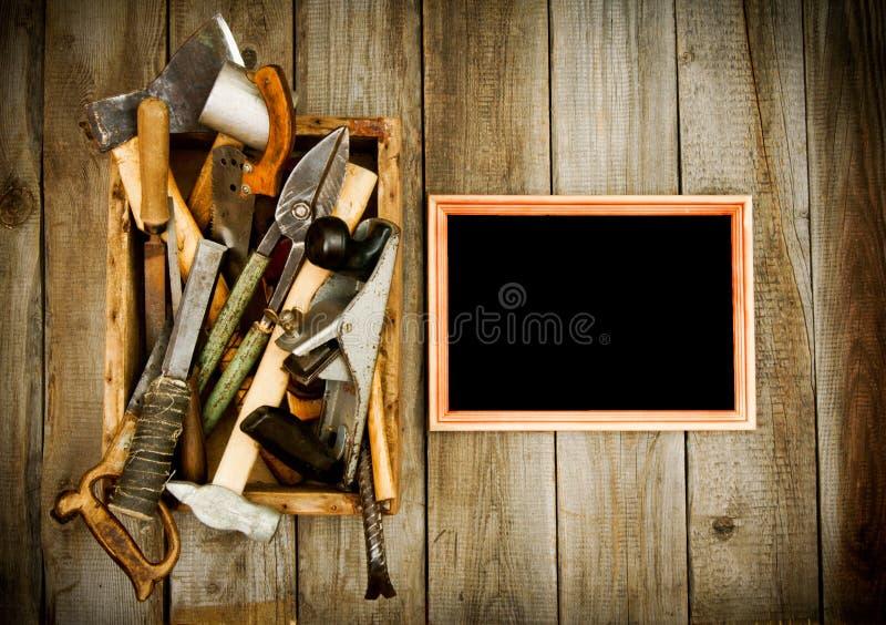 Quadro com ferramentas velhas (tesouras, alicates, serra e fotos de stock royalty free