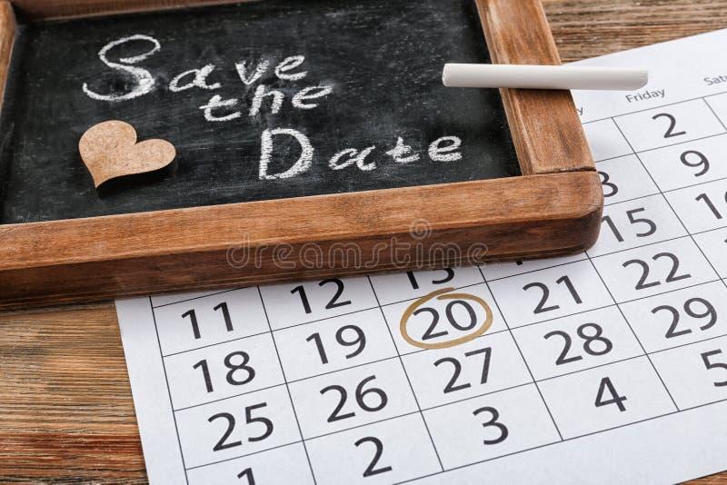 """Quadro com inscrição \ """"economias a data \"""" e calendário na tabela de madeira imagem de stock royalty free"""