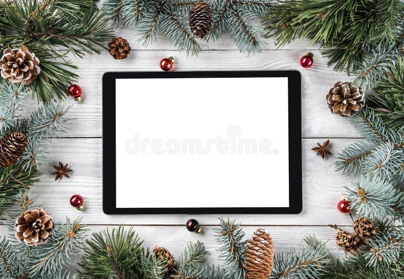 Quadro criativo da disposição feito de ramos de árvore do Natal, de cones do pinho e de PC da tabuleta no fundo de madeira branco foto de stock royalty free