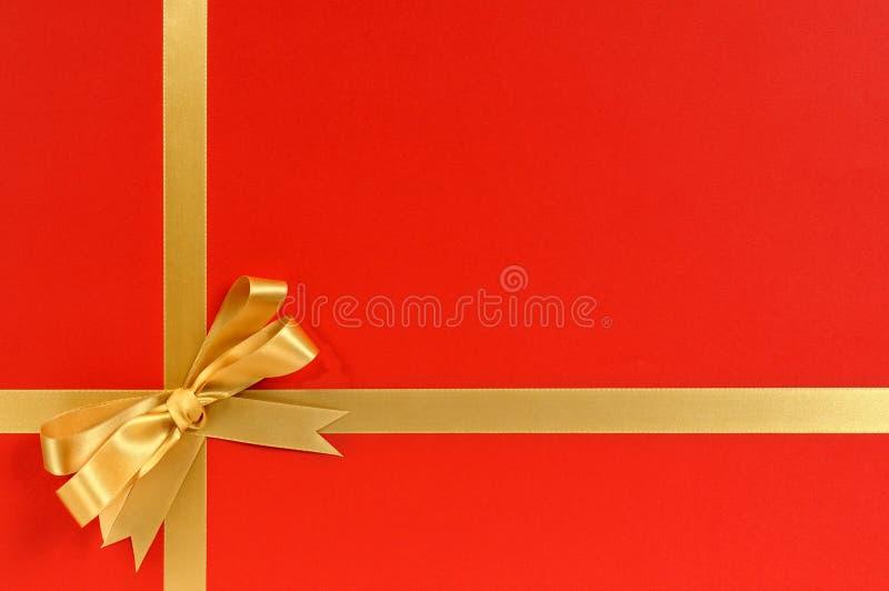 Quadro da beira do presente do Natal com fita do ouro e fundo do vermelho da curva fotografia de stock