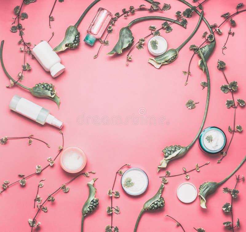 Quadro da beleza com os vários produtos cosméticos faciais com zombaria acima, folhas e as flores verdes no fundo do desktop do r imagem de stock royalty free