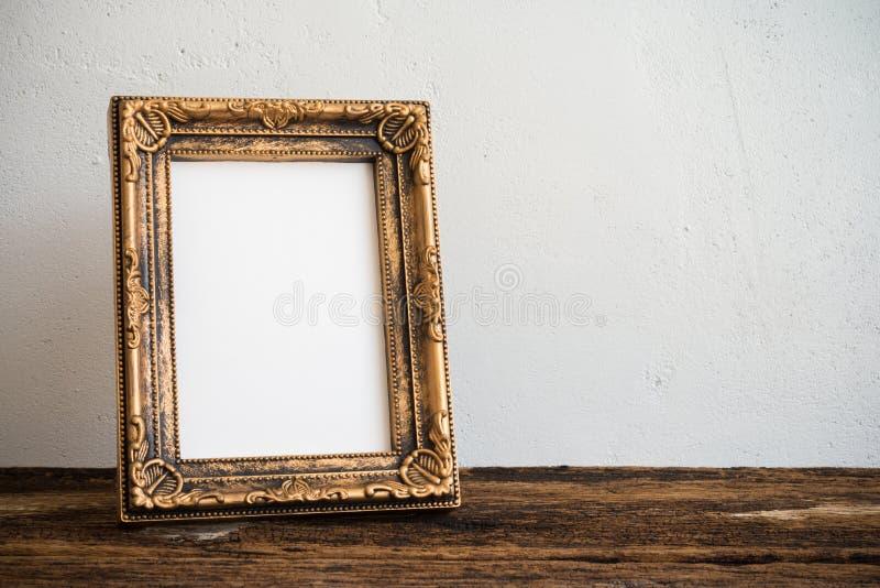 Quadro da foto do vintage na tabela de madeira velha sobre o backgrou branco da parede imagem de stock royalty free