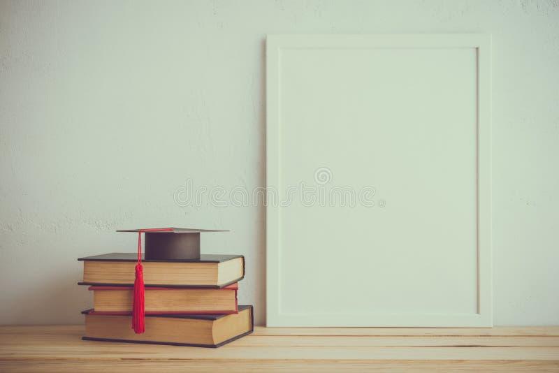 Quadro da foto e livros, chapéu do graducation no fundo branco da parede, foto de stock