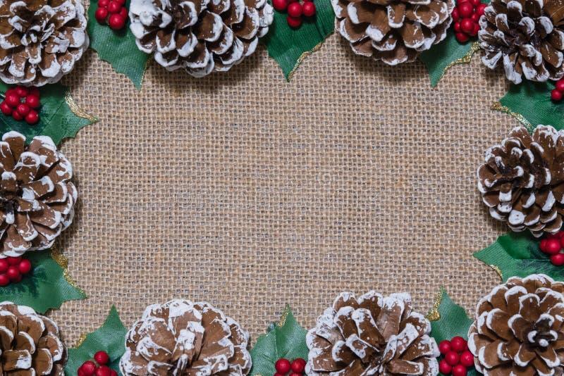 Quadro da liso-configuração do Natal dos pinecones, das folhas do azevinho, e de bagas vermelhas no fundo rústico da tela fotos de stock royalty free