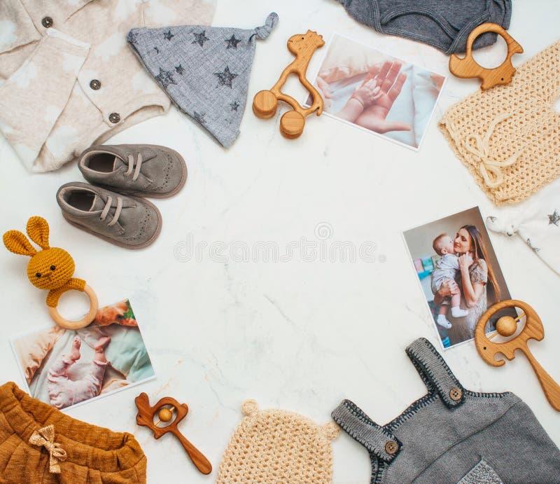 Quadro da roupa recém-nascida do bebê, brinquedos no fundo de mármore claro imagens de stock royalty free