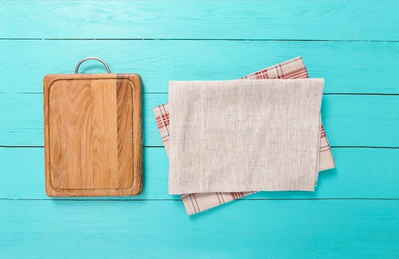 Quadro da toalha de mesa de madeira da cozinha da placa e da manta de corte na tabela azul Espaço da vista superior e da cópia Lu imagem de stock royalty free