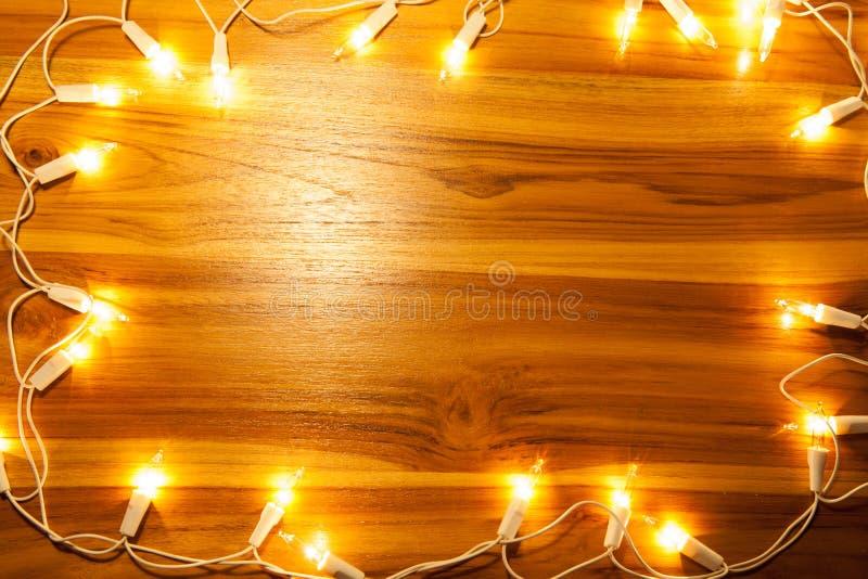 Quadro das luzes de Natal em de madeira dourado imagem de stock