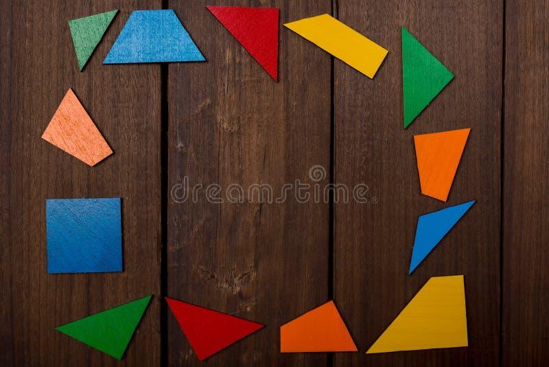 Quadro das partes coloridas do jogo lógico de madeira na tabela marrom de madeira Copie o espaço imagens de stock royalty free