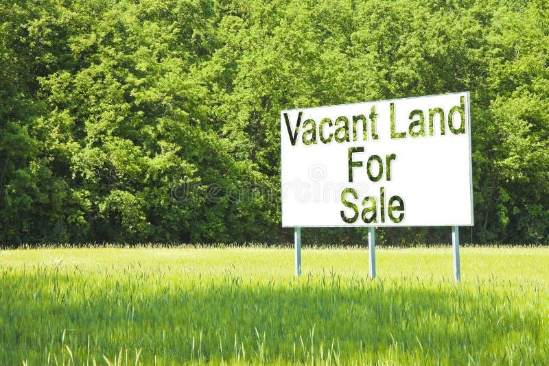 Quadro de avisos de propaganda imergido em uma cena rural com terra vaga para a venda escrita nela - imagem com espaço da cópia fotografia de stock