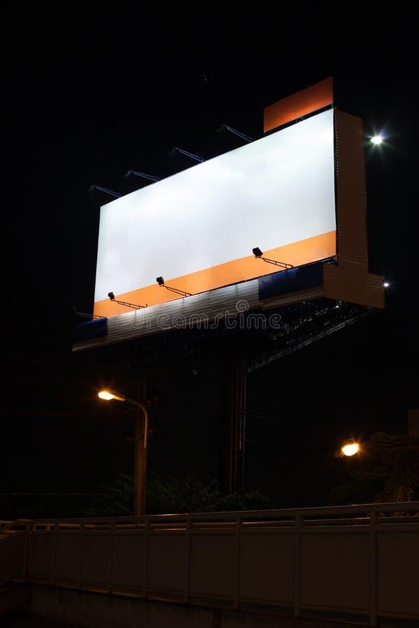 Quadro de avisos vazio da propaganda com fundo branco do espaço vazio na noite acima da ponte pedestre através da estrada princip imagens de stock