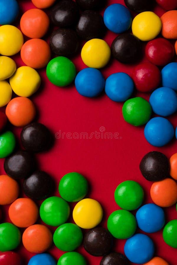 Quadro de doces multicoloridos com um espaço livre em um fundo vermelho imagem de stock royalty free