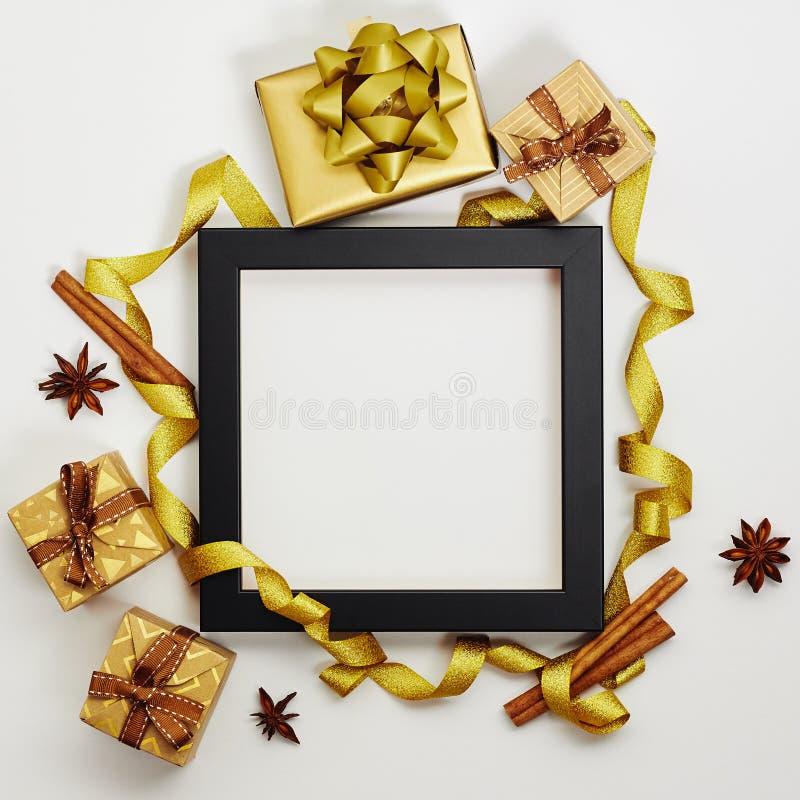 Quadro de fundo de Natal e Ano Novo Caixas de presentes com fita dourada, anis-estrela e canela sobre fundo branco fotos de stock royalty free