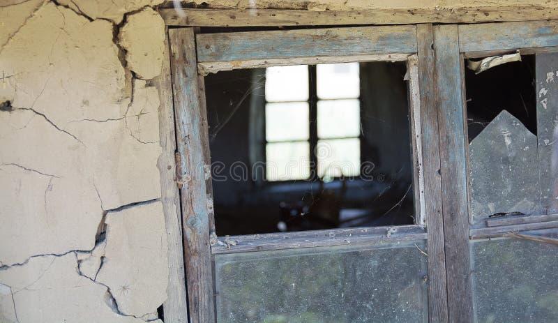Quadro de janela de madeira velho deteriorado com a placa de janela quebrada imagens de stock
