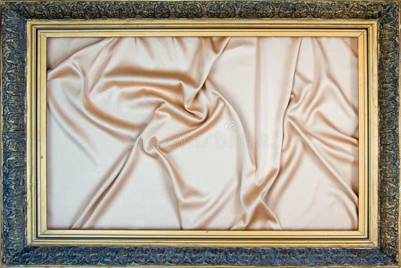 Quadro de madeira antigo com mentiras da folha de ouro em uma seda bege chique, fundo fotos de stock royalty free