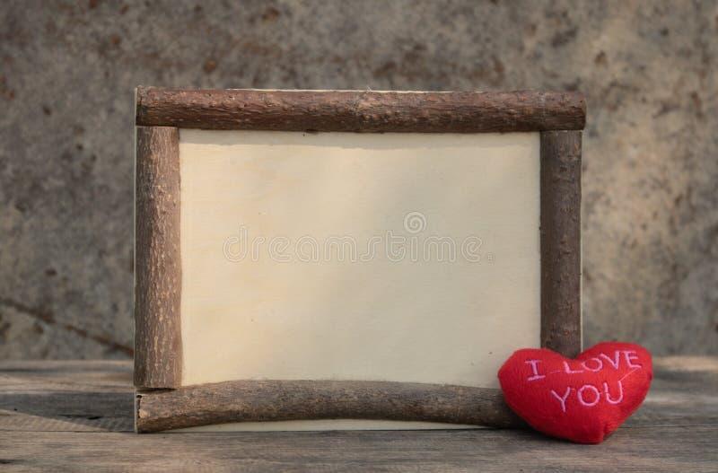 Quadro de madeira com cora??o vermelho na tabela de madeira imagem de stock