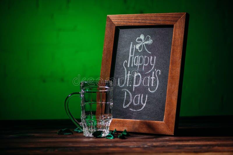 quadro de madeira com inscrição feliz do dia dos patricks do st e vidro de cerveja vazio imagem de stock
