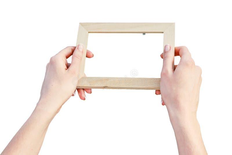 Quadro de madeira da foto nas mãos de uma mulher foto de stock