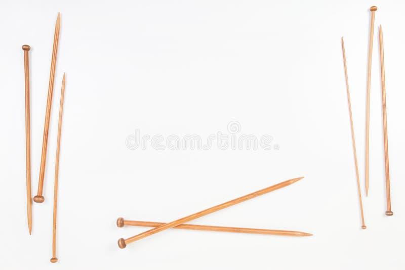 Quadro de madeira das agulhas de confecção de malhas com espaço da cópia para o texto no fundo branco foto de stock