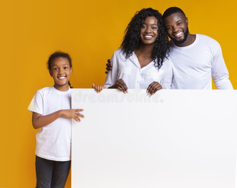 Quadro de propaganda branco em branco em mãos de uma família negra feliz imagem de stock royalty free
