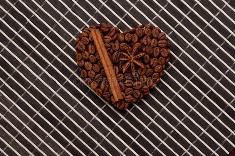 Quadro do café do coração feito de feijões de café na textura de madeira, canela fotografia de stock royalty free