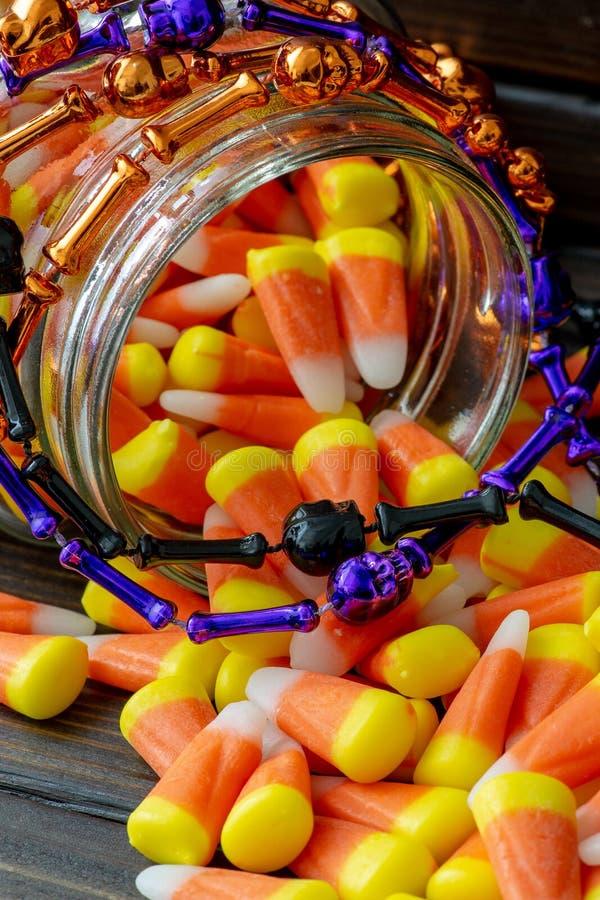 Quadro do fundo de Dia das Bruxas que consiste em um frasco completamente do milho de doces em uma tabela de madeira escura com u fotos de stock royalty free
