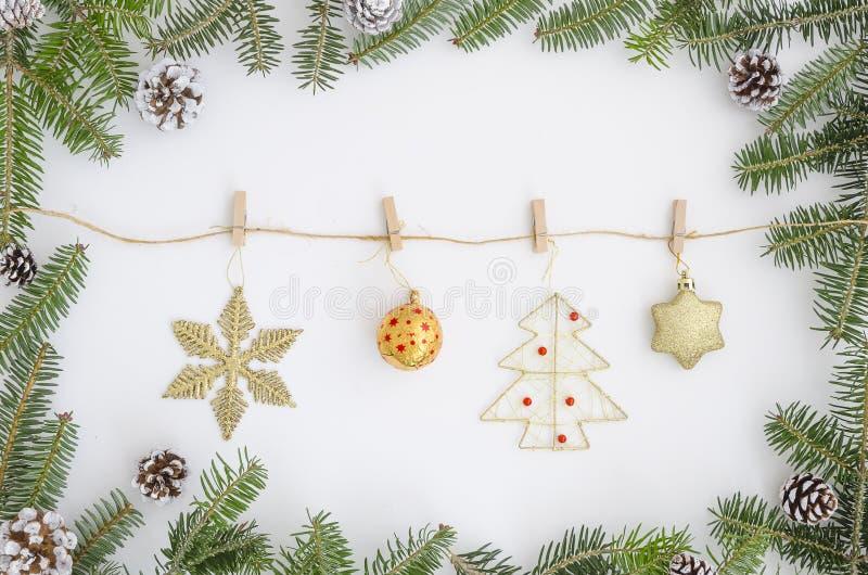 Quadro do Natal feito de ramos do abeto da árvore de Natal Oon a corda com os pregadores de roupa que penduram brinquedos, uma es fotos de stock