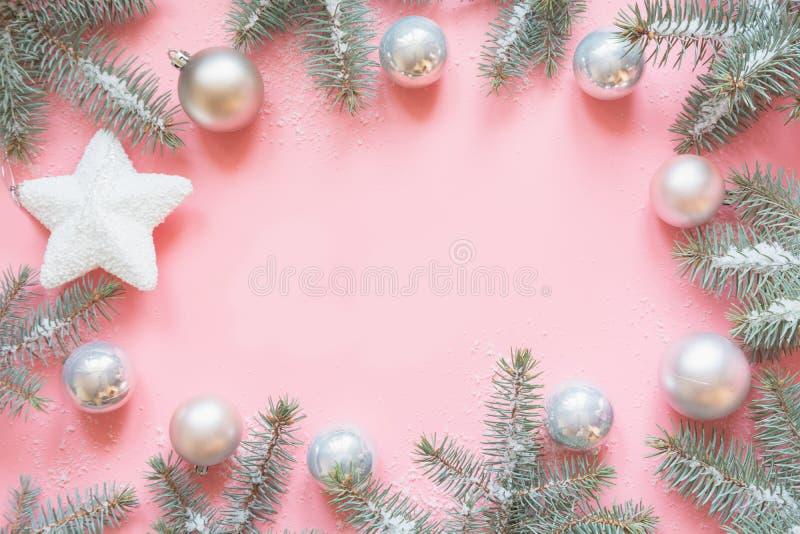 Quadro do Natal feito de ramos do abeto, decorações brancas nevados, bolas brancas da estrela na tabela cor-de-rosa Fundo do Xmas fotos de stock