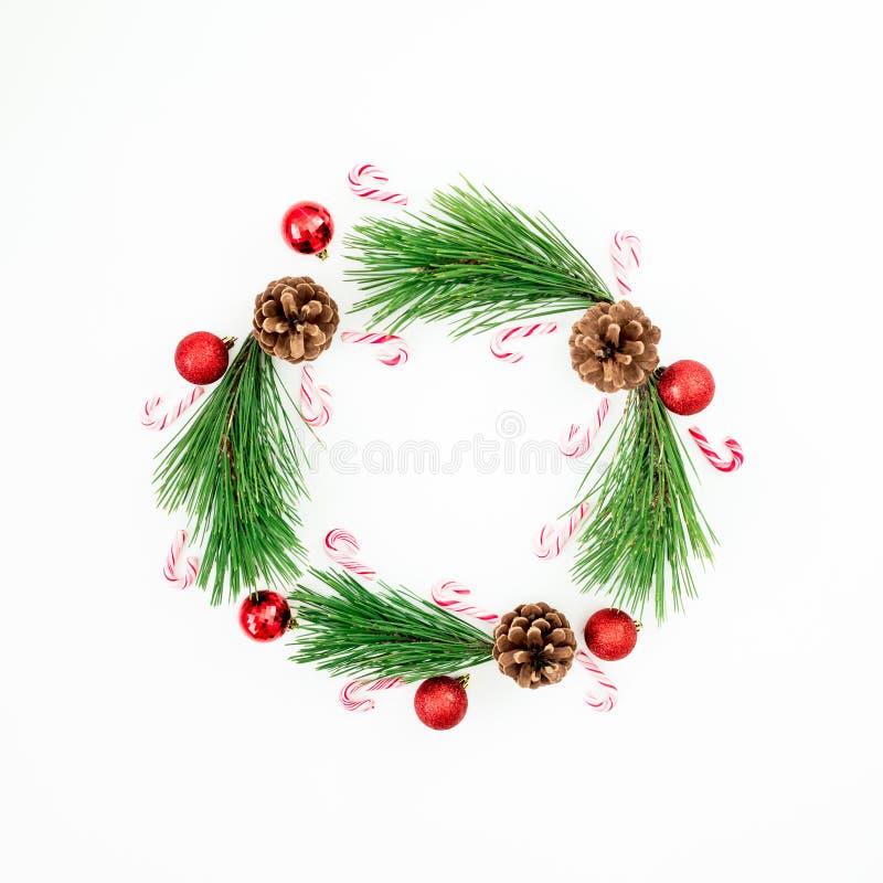 Quadro do Natal feito de ramos do pinho e da decoração vermelha das bolas com o bastão de doces no fundo branco Fundo festivo Con imagens de stock royalty free