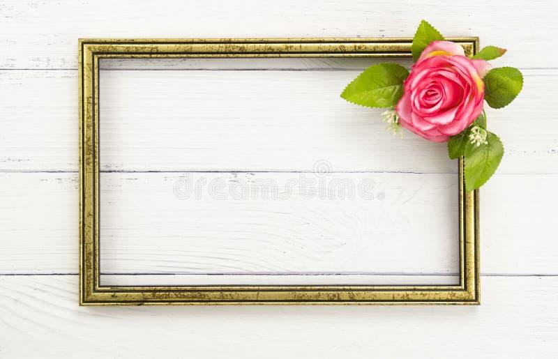 Quadro do ouro e uma rosa cor-de-rosa fotos de stock