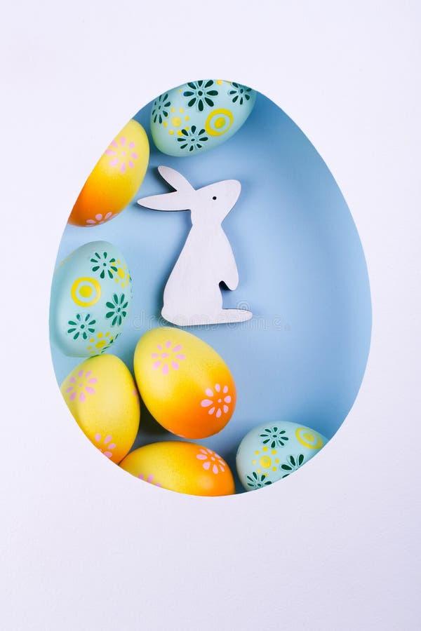 Quadro do ovo da páscoa feito do papel, ovos pintados coloridos da galinha, coelho de madeira branco no fundo azul Compisition de foto de stock