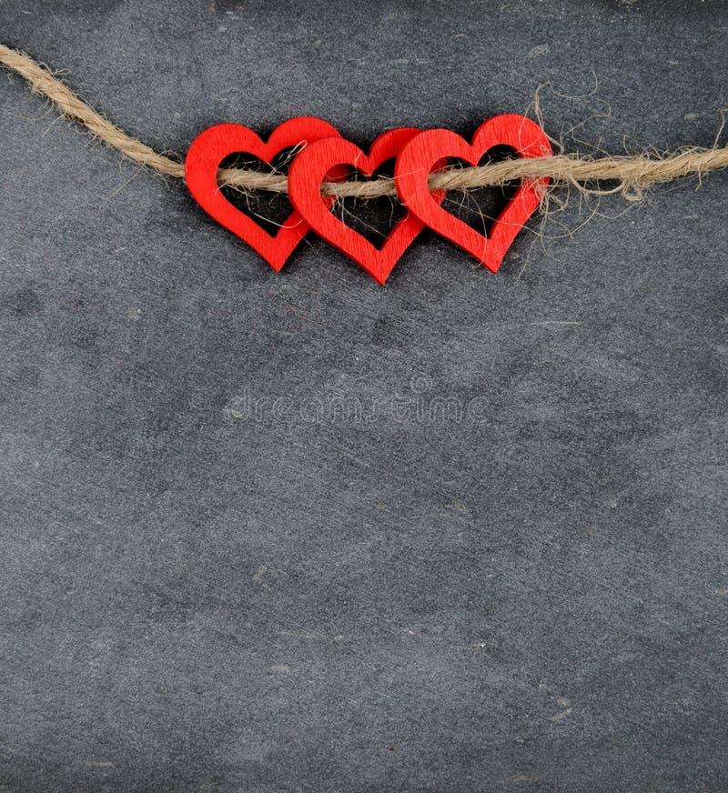 Quadro do vintage com três símbolos vermelhos da forma do coração na corda imagens de stock royalty free
