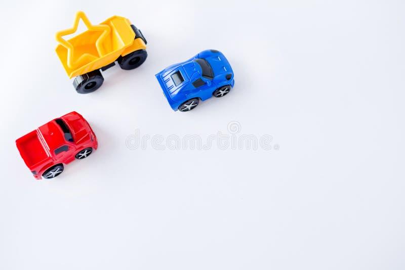 Quadro dos carros dos brinquedos das crianças no fundo branco Vista superior Configuração lisa Copie o espaço para o texto imagens de stock royalty free