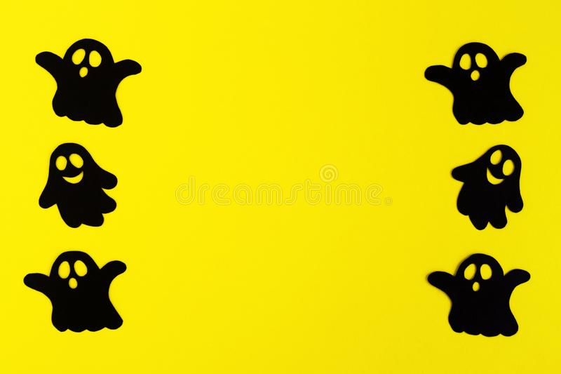 Quadro dos fantasmas de papel pretos em um fundo amarelo Decorações do feriado para Dia das Bruxas com espaço da cópia imagem de stock royalty free
