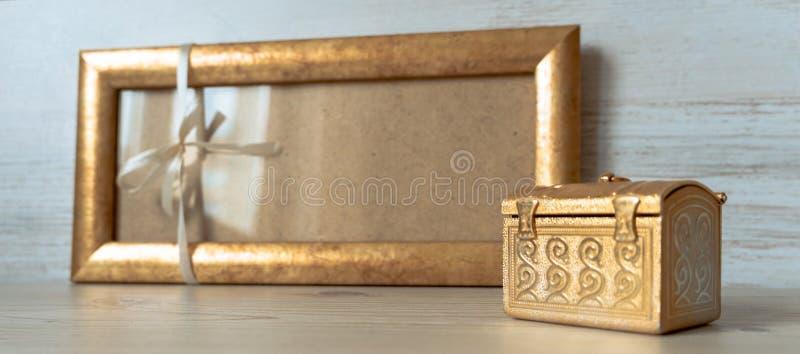 Quadro dourado com uma curva branca e caixa dourada no fundo de madeira cinzento imagens de stock royalty free