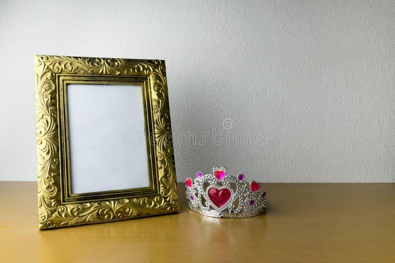 Quadro e coroa da foto na tabela de madeira fotografia de stock royalty free