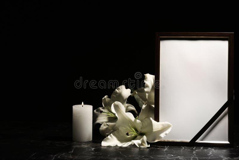 Quadro fúnebre da foto, vela ardente e flores do lírio imagens de stock