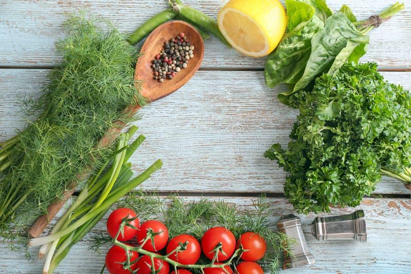 Quadro feito de ervas, de especiarias, de vegetais e do limão frescos diferentes no fundo de madeira foto de stock