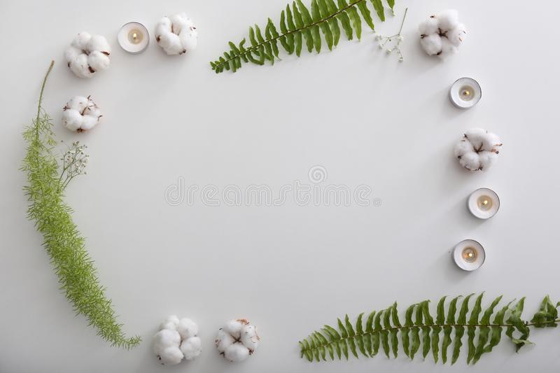 Quadro feito de velas de queimadura, de flores do algodão e das folhas tropicais no fundo branco fotografia de stock