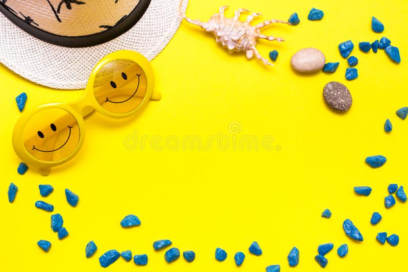 Quadro feito dos óculos de sol com um sorriso, um chapéu, umas pedras decorativas e um escudo em um fundo amarelo fotografia de stock