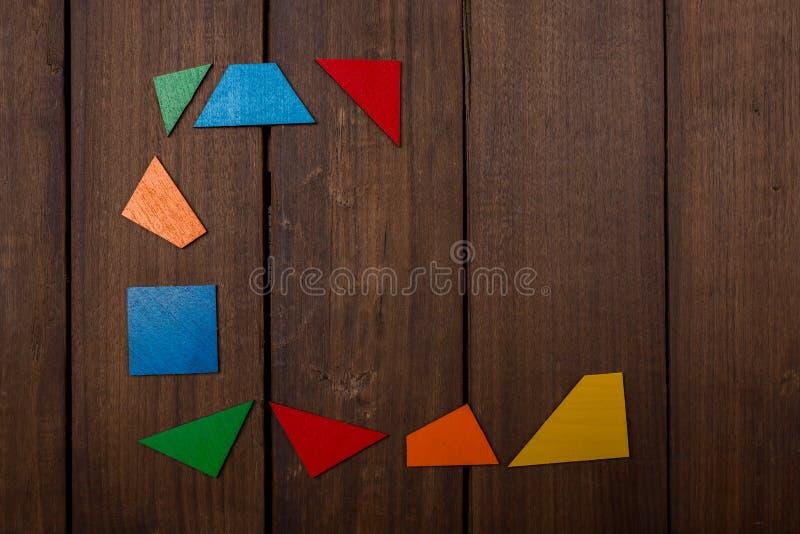 Quadro inacabado das partes coloridas do jogo lógico de madeira na tabela marrom de madeira Copie o espaço imagem de stock