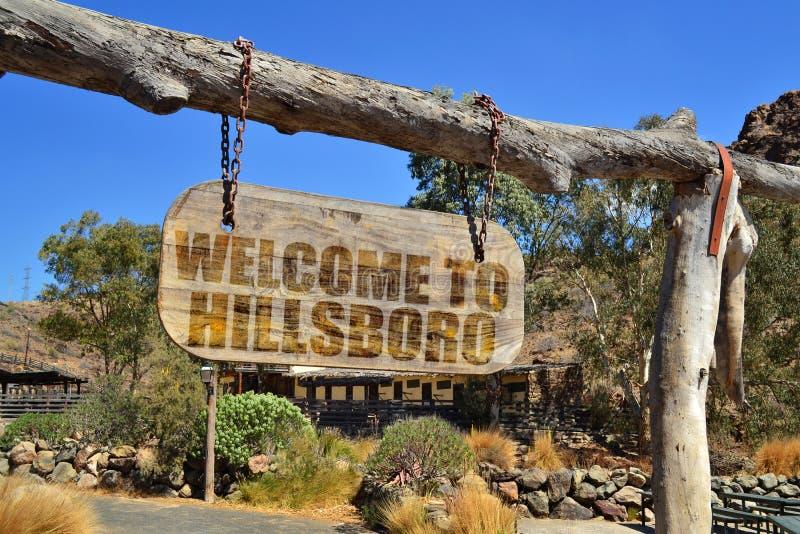 quadro indicador de madeira velho com boa vinda do texto a Hillsboro suspensão em um ramo imagem de stock