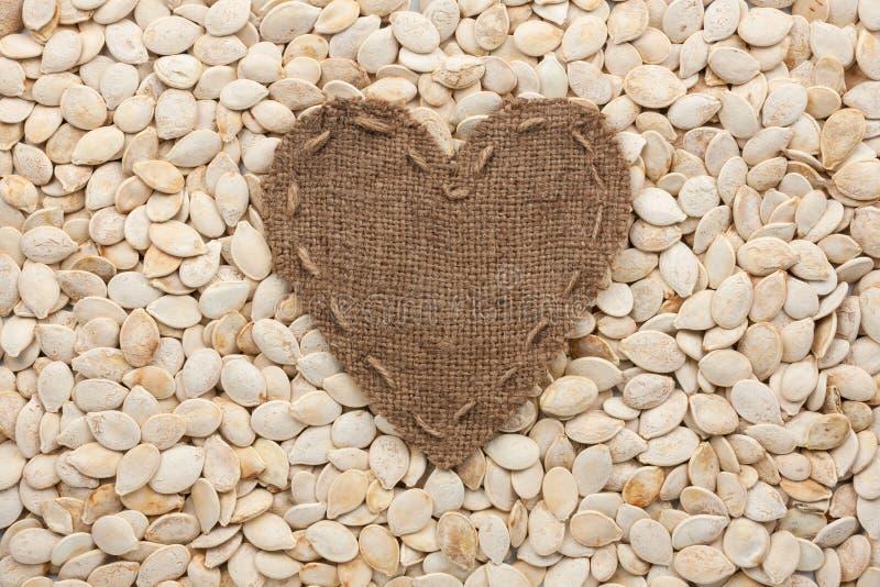 Quadro na forma do coração feita da serapilheira com sementes de abóbora imagens de stock royalty free