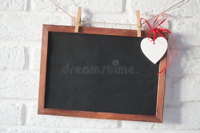 Quadro-negro com coração de madeira nos pinos fotografia de stock