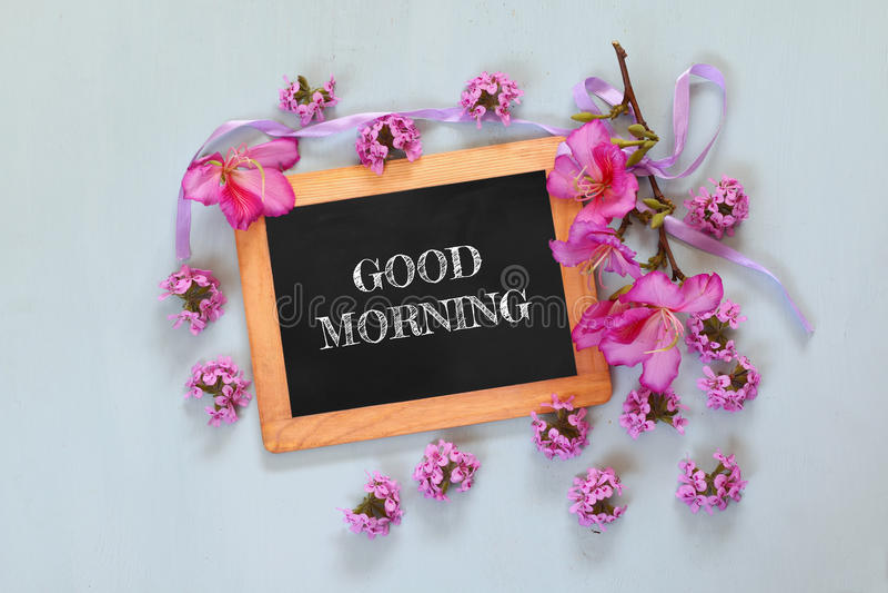 Quadro-negro com o bom dia da frase escrito nele ao lado das flores frescas foto de stock