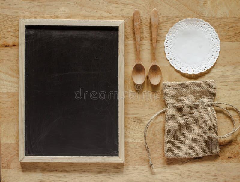 Quadro-negro com serapilheira e colher fotografia de stock