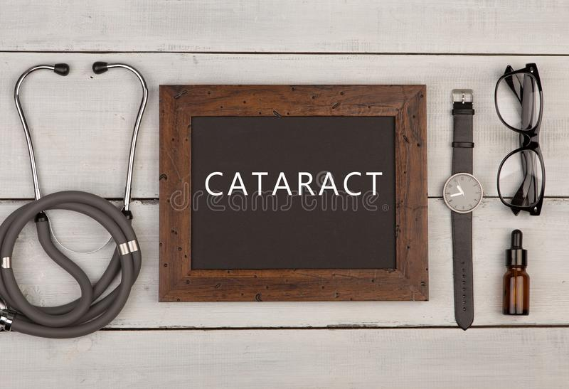 quadro-negro com texto & x22; Cataract& x22; , estetoscópio, monóculos e relógio fotos de stock royalty free