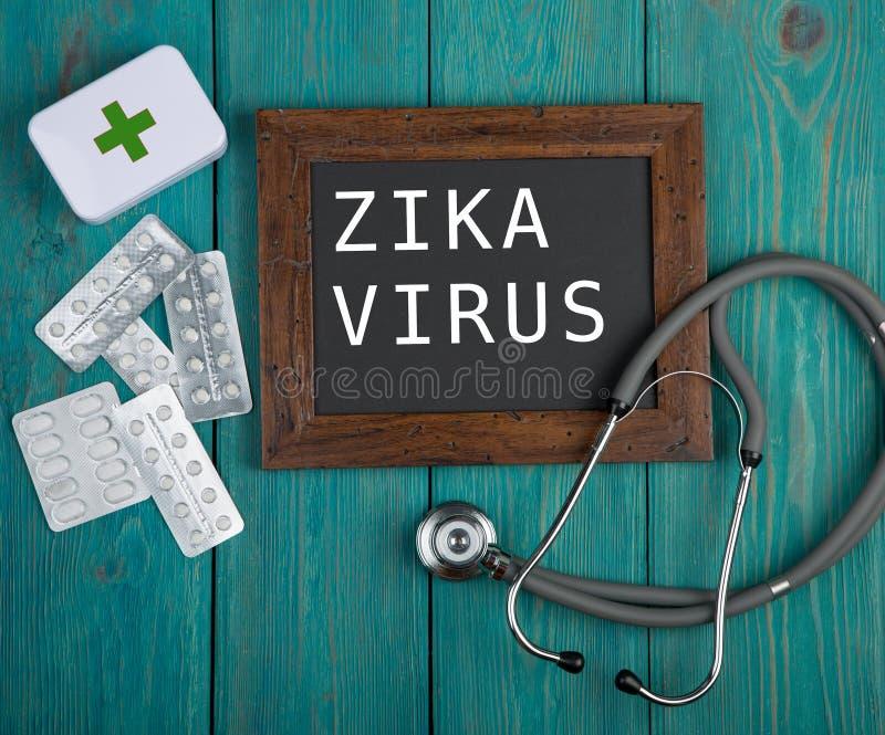 Quadro-negro com texto & x22; Virus& x22 de Zika; , comprimidos e estetoscópio no fundo de madeira azul fotografia de stock royalty free