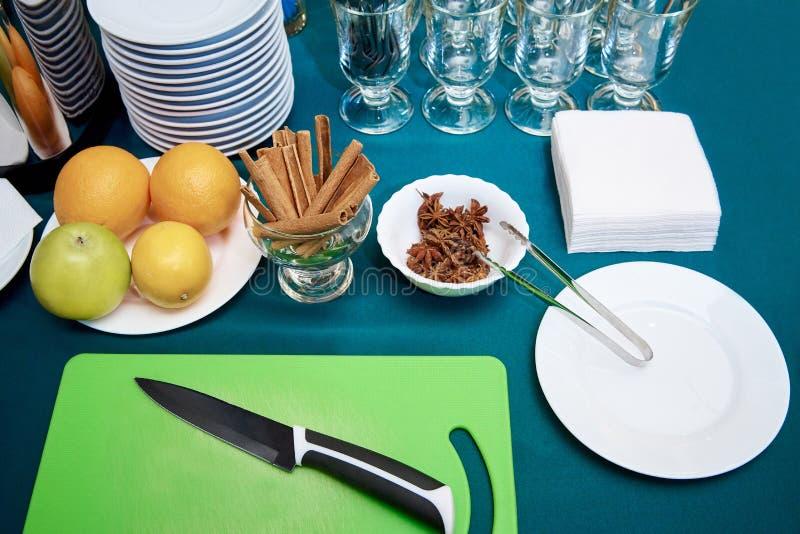 Quadro-negro com uma faca de cozinha, um fruto fresco e uma canela na tabela com placas e vidros fotos de stock