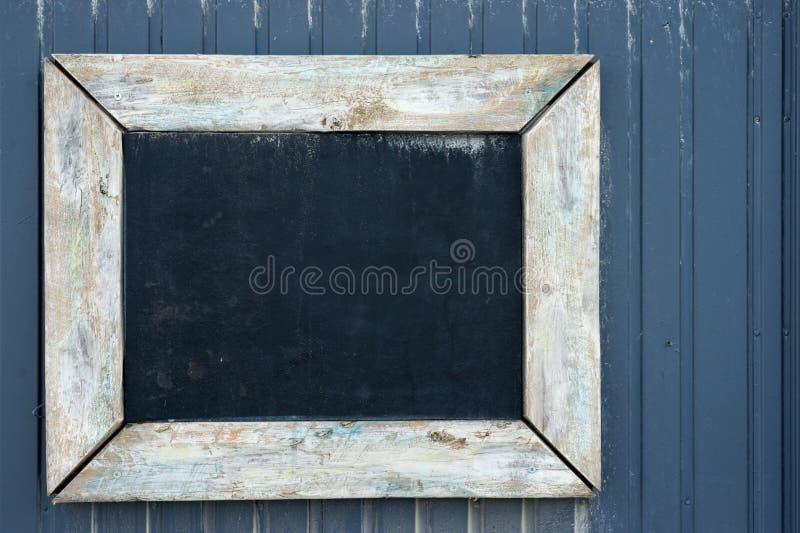 Quadro-negro do vintage em uma parede de madeira foto de stock